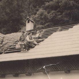 Doi bărbați și un băiat reparând un acoperiș